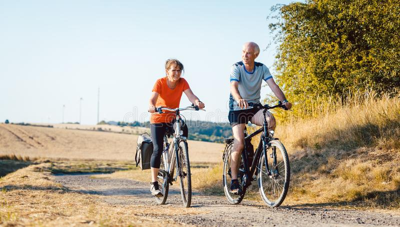 Ältere Paare, die ihr Fahrrad für bessere Eignung fahren stockfotos
