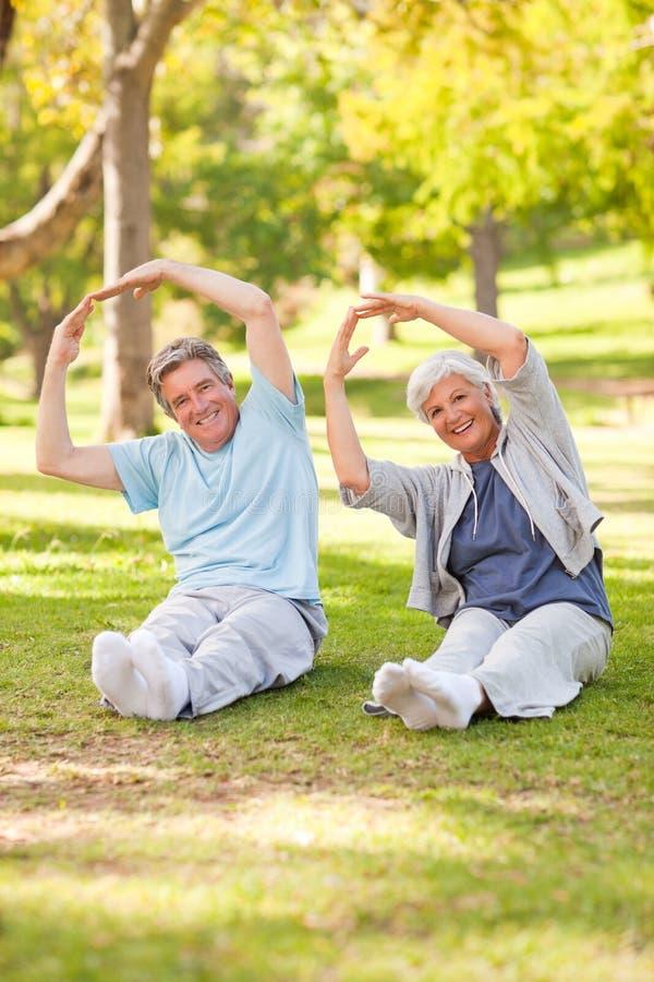 Ältere Paare, die ihre Ausdehnungen tun lizenzfreies stockbild