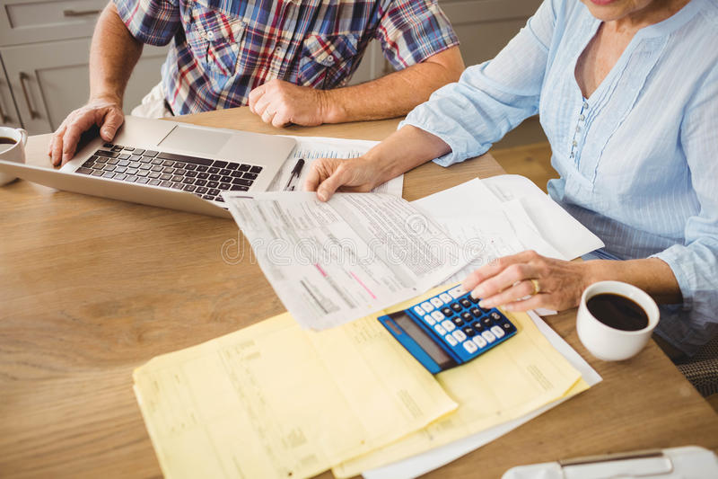 Ältere Paare, die ihre Rechnungen überprüfen stockfotografie