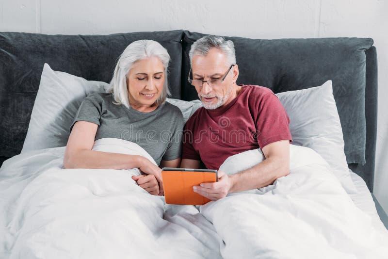 Ältere Paare, die im Bett liegen und zusammen Tablette verwenden stockfotografie