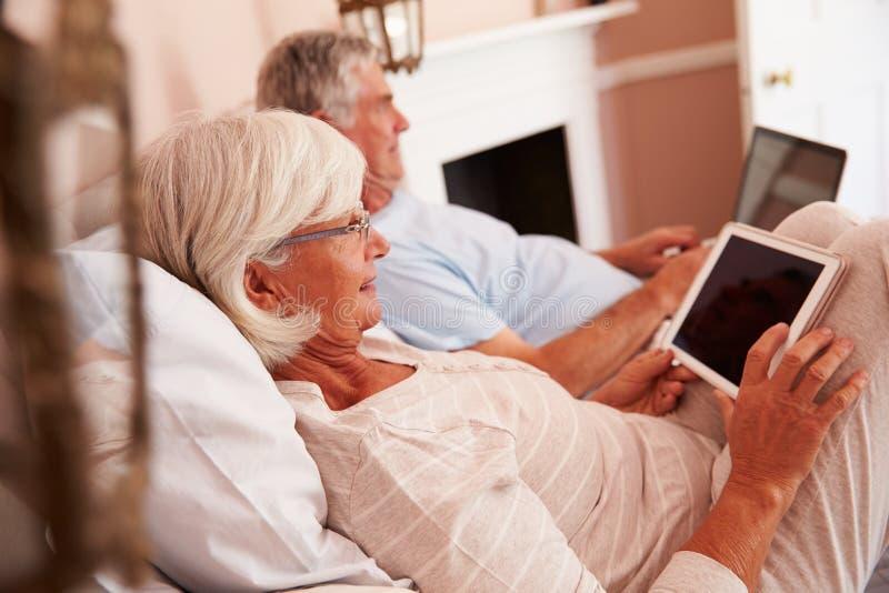 Ältere Paare, die im Bett unter Verwendung Digital-Geräte liegen lizenzfreie stockfotos