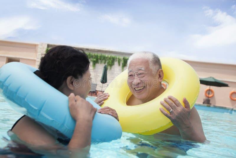 Ältere Paare, die im Pool mit aufblasbaren Rohren lächeln und sich entspannen lizenzfreie stockfotos