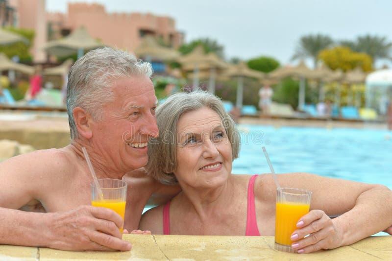 Ältere Paare, die im Pool sich entspannen lizenzfreie stockfotografie