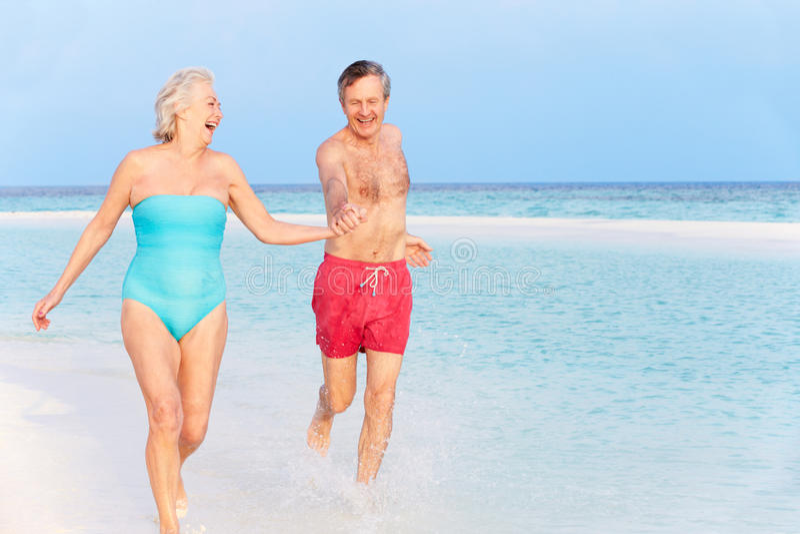 Ältere Paare, die im schönen tropischen Meer spritzen stockfotos
