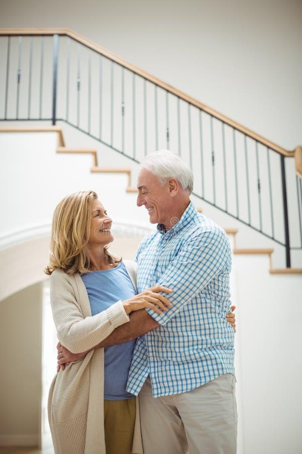 Ältere Paare, die im Wohnzimmer sich umfassen stockfotografie