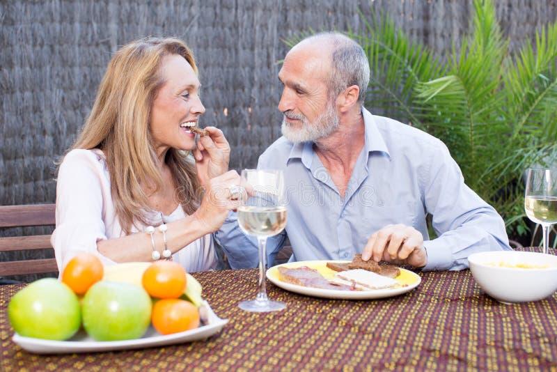 Ältere Paare, die Lebensmittel auf Terrasse essen stockbild