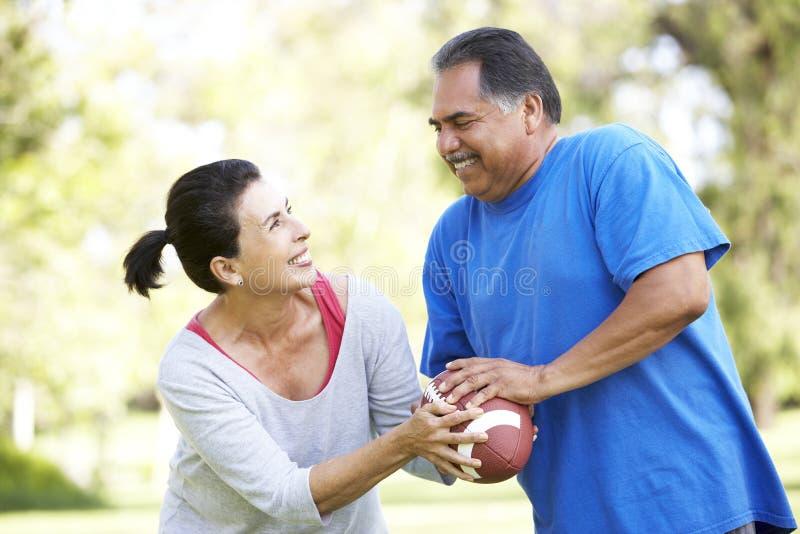 Ältere Paare, die mit amerikanischem Fußball trainieren stockfotografie