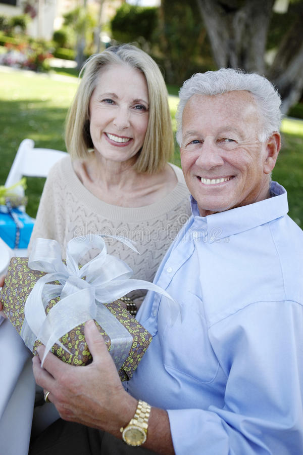 Ältere Paare, die mit einem Geschenk im Garten sitzen stockbild