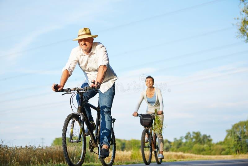 Ältere Paare, die mit Fahrrädern radfahren lizenzfreie stockbilder