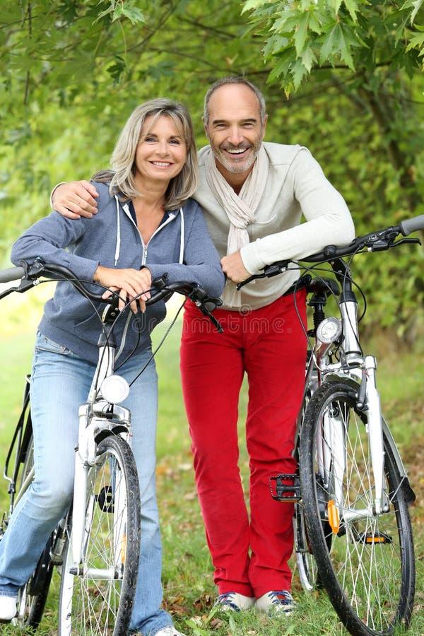 Ältere Paare, die nachdem Fahrrad sich entspannen, gefahren worden ist stockbilder