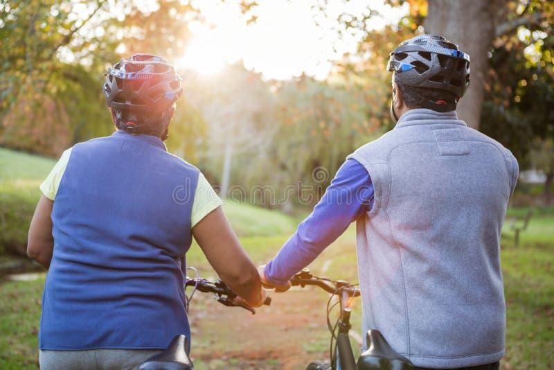 Ältere Paare, die nahe bei ihrem Fahrrad gehen stockbilder