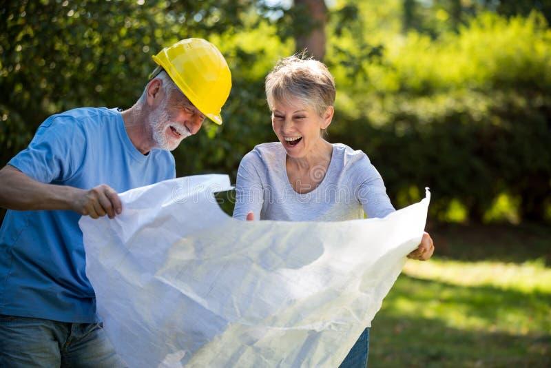 Ältere Paare, die Plan im Garten betrachten stockbild