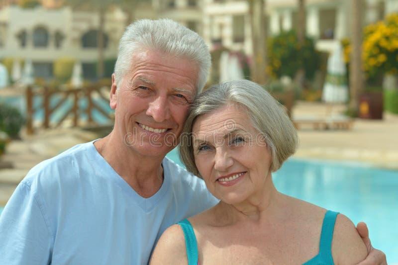 Ältere Paare, die am Pool sich entspannen lizenzfreie stockbilder