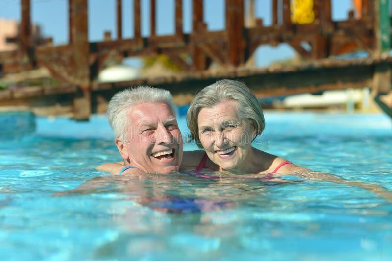 Ältere Paare, die am Pool sich entspannen stockbild