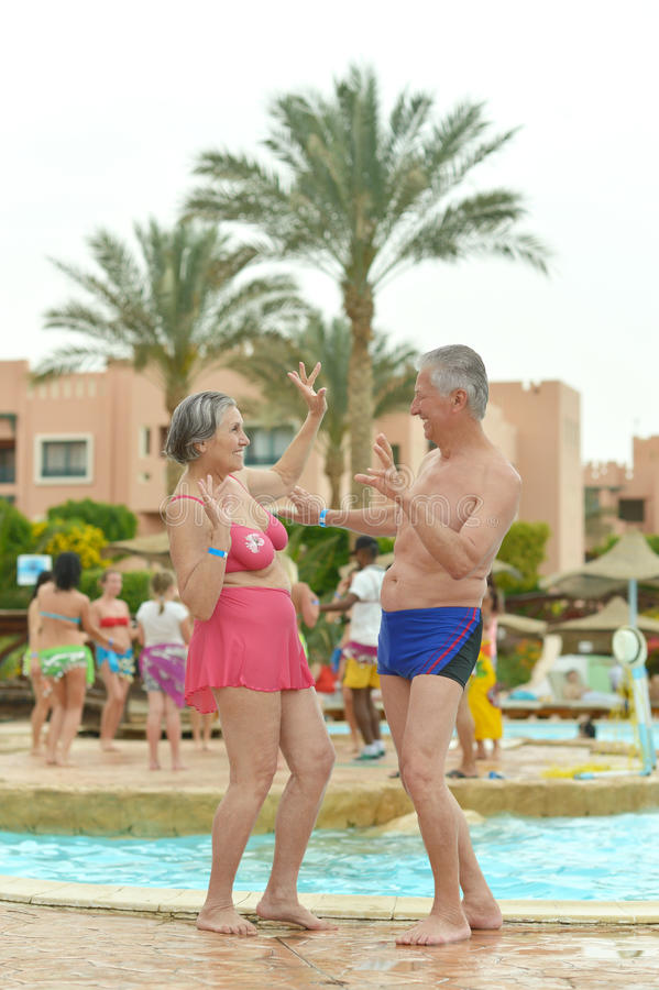 Ältere Paare, die in am Pool stehen stockfoto