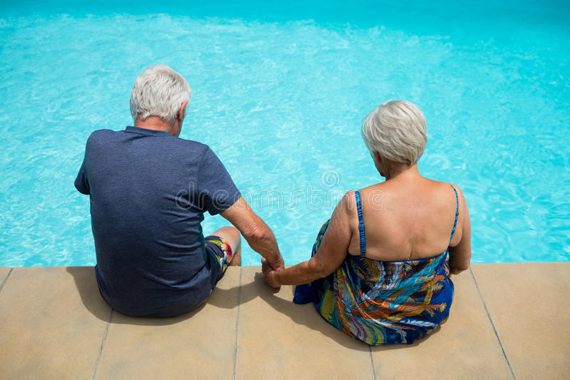 Ältere Paare, die am Poolside sich entspannen stockbild