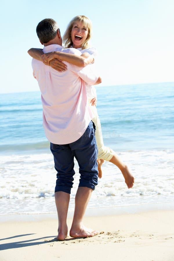 Ältere Paare, die romantischen Strand-Feiertag genießen stockfotos