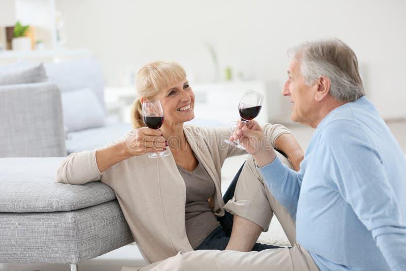 Ältere Paare, die Rotwein trinkend genießen stockbilder