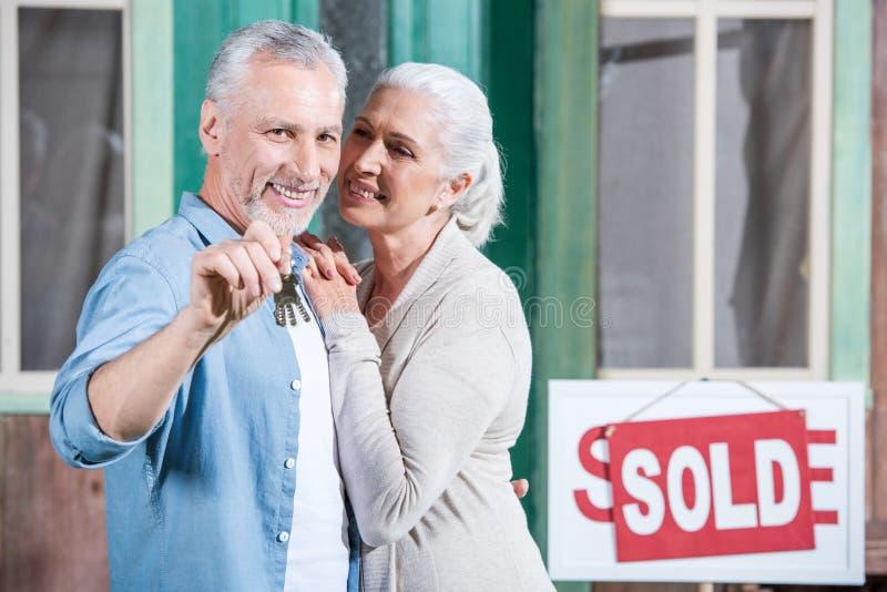 Ältere Paare, die Schlüssel ihres neuen Hauses halten und auf Portal umarmen stockfotos