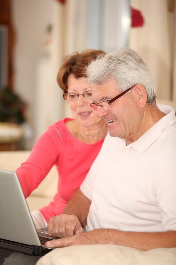 Ältere Paare, die sich zu Hause mit Laptop entspannen lizenzfreies stockfoto