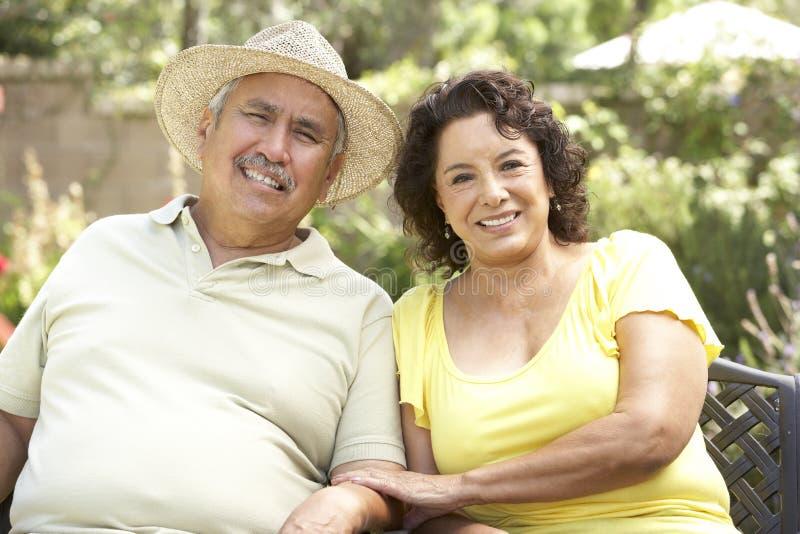 Ältere Paare, die sich zusammen im Garten entspannen lizenzfreie stockfotos