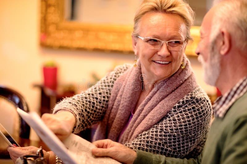 Ältere Paare, die Spaß beim Ablesen der Zeitung und Anwendung der Tabelle haben stockfotos