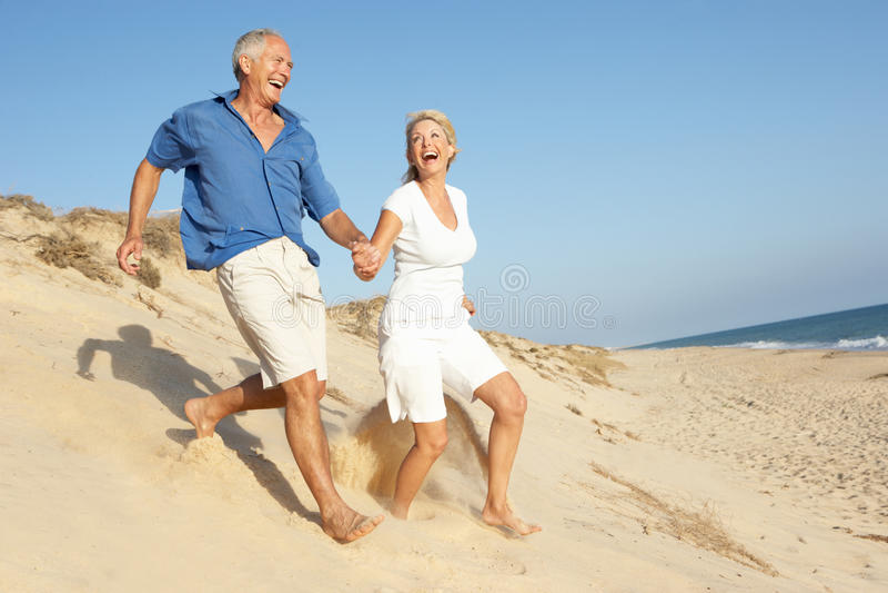 Ältere Paare, die Strand-Feiertags-Betrieb genießen stockfotos