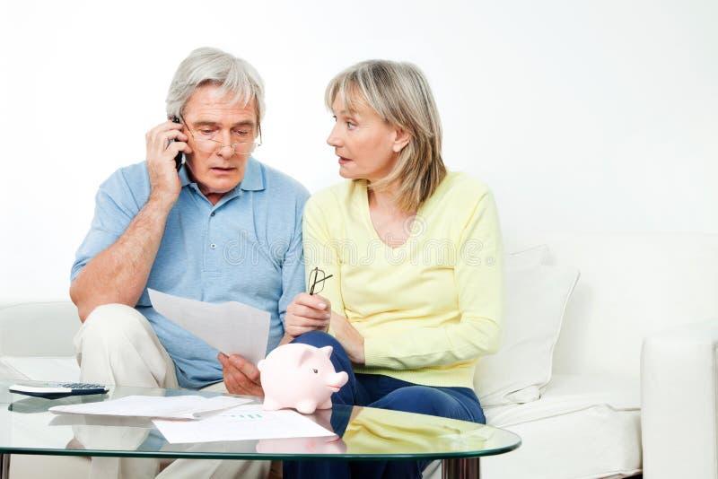 Ältere Paare, die am Telefon sich beschweren stockbild