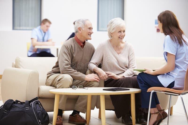 Ältere Paare, die Testergebnisse mit Krankenschwester besprechen stockbild