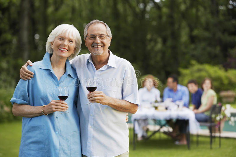 Ältere Paare, die Wein-Gläser im Hinterhof halten stockbilder