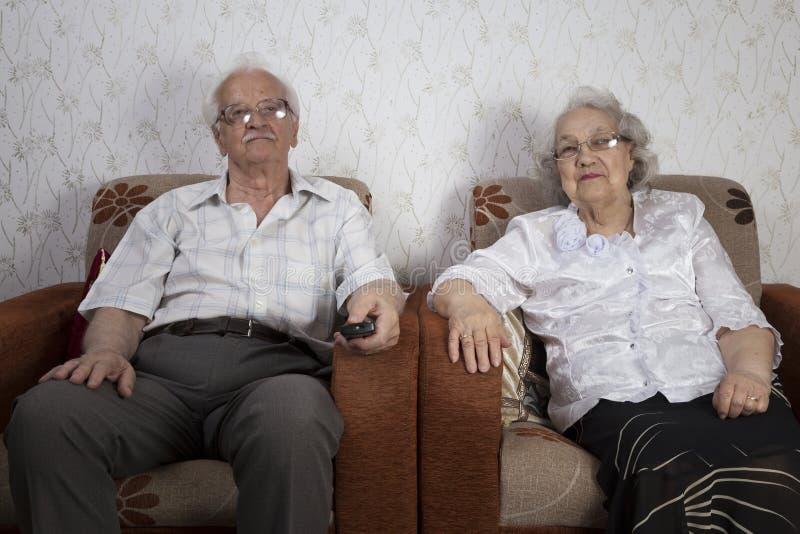 Ältere Paare, die zu Hause Fernsehen stockbilder