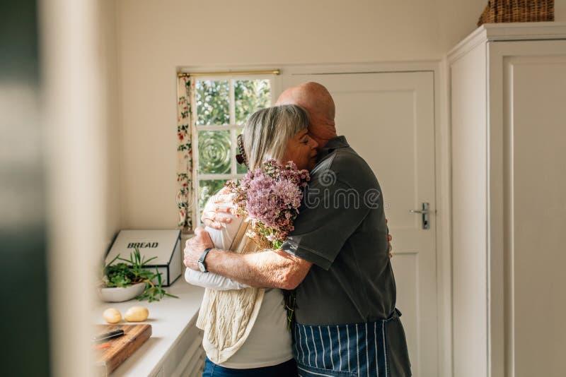 Ältere Paare, die zu Hause Stellung umfassen lizenzfreies stockbild