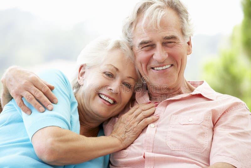 Ältere Paare, die zusammen auf Seat im Freien sitzen lizenzfreies stockbild