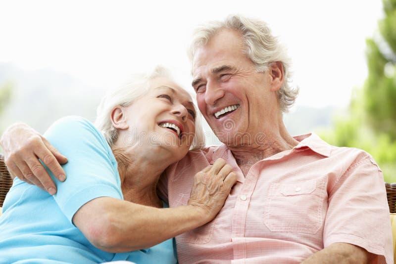 Ältere Paare, die zusammen auf Seat im Freien sitzen stockfoto