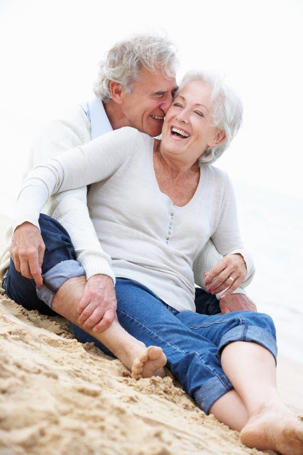 Ältere Paare, die zusammen auf Strand sitzen stockfoto