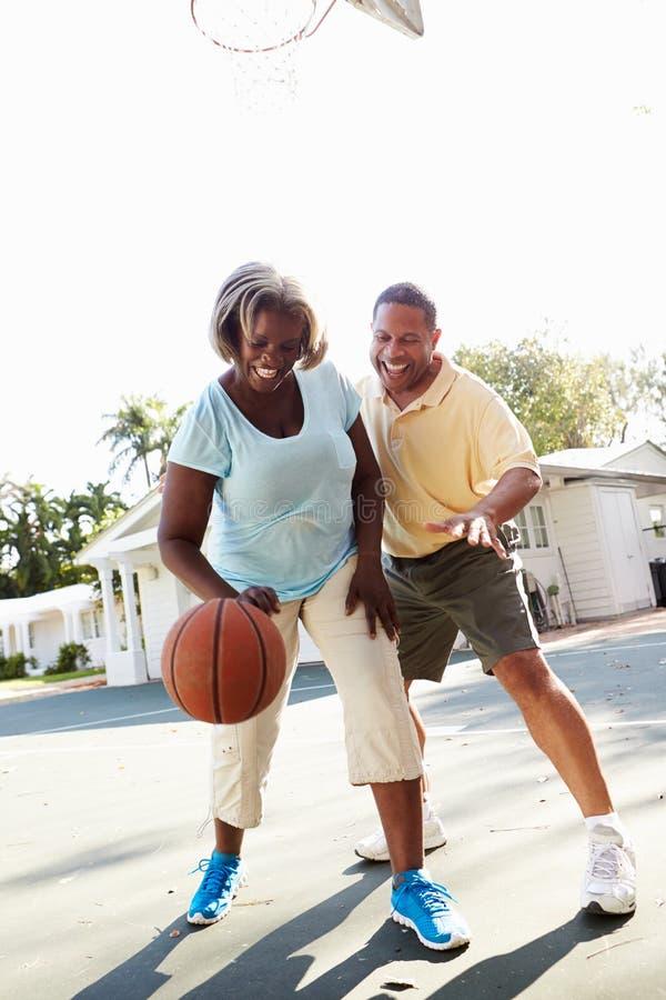 Ältere Paare, die zusammen Basketball spielen stockfotografie
