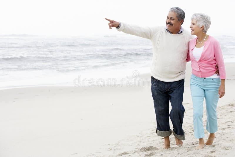 Ältere Paare, die zusammen entlang Strand gehen stockbild