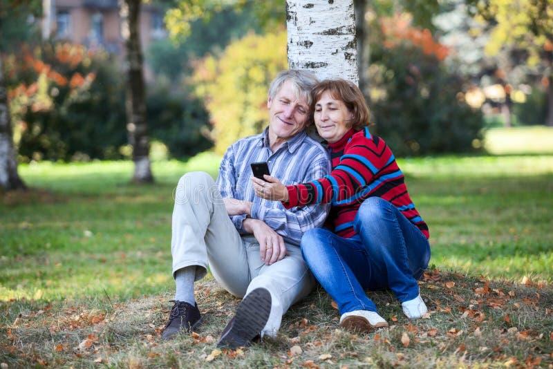 Ältere Paare, die zusammen sitzen und selfie mit Mobiltelefon im Park machen stockfotos