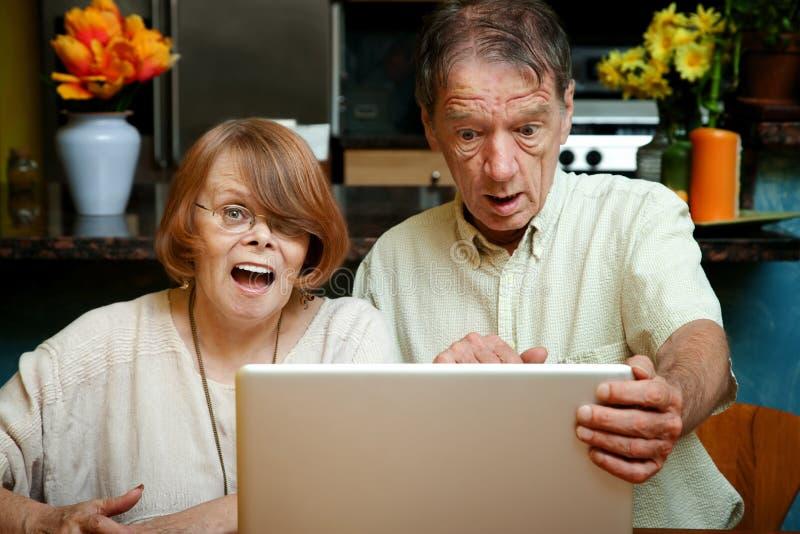 Ältere Paare entsetzt am Inhalt auf ihrem Baut. stockfotografie