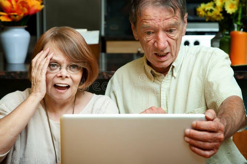 Ältere Paare entsetzt am Inhalt auf ihrem Baut. lizenzfreie stockbilder