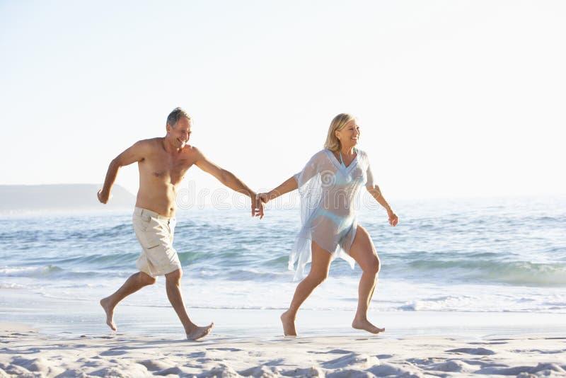 Ältere Paare am Feiertag, der entlang Sandy Beach Looking Out To-Meer läuft lizenzfreies stockbild
