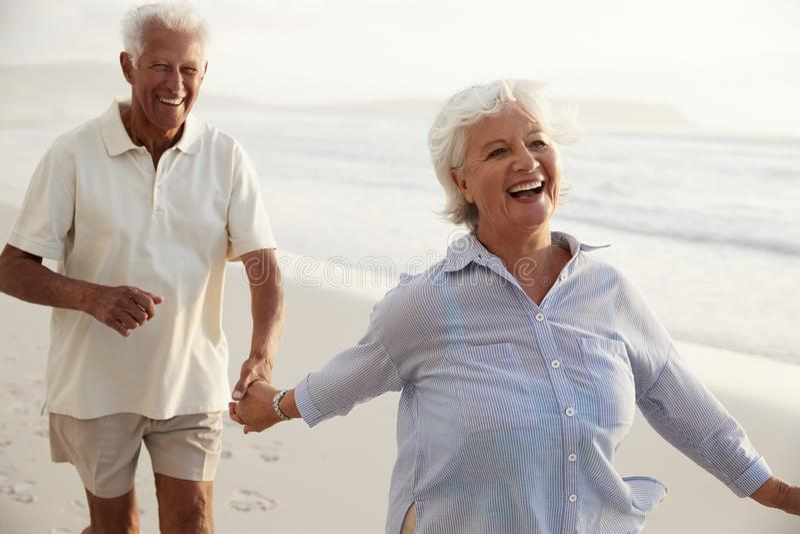 Ältere Paare im Ruhestand, die Hand in Hand entlang Strand zusammen laufen stockbild