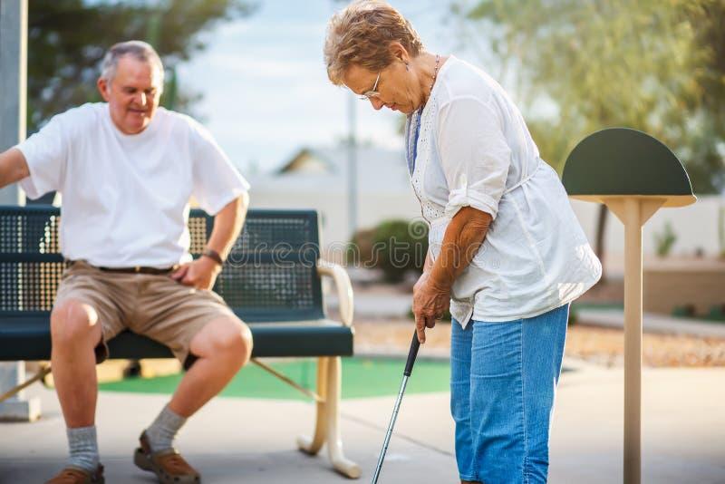Ältere Paare im Ruhestand, die zusammen Minigolf spielen stockbild