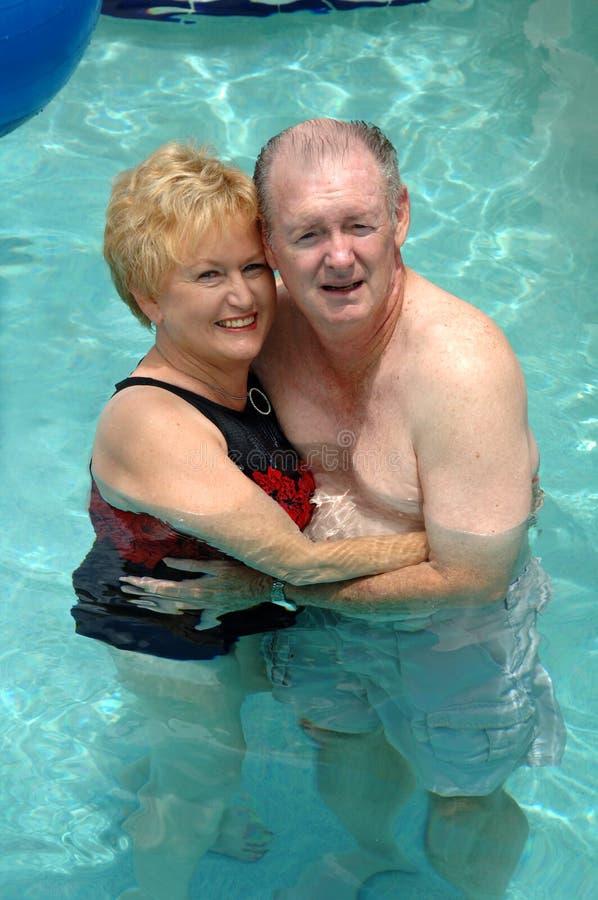 Ältere Paare im Swimmingpool stockfotografie