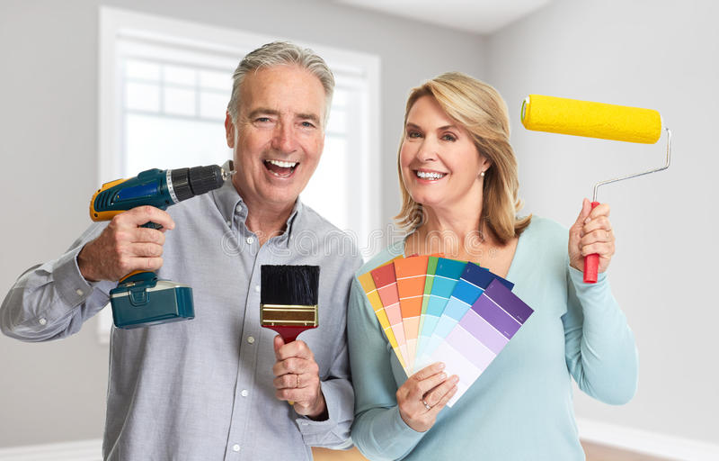 Ältere Paare mit Bohrgerät- und Malereirolle lizenzfreie stockfotos