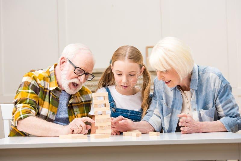 Ältere Paare mit der Enkelin, die zu Hause jenga Spiel spielt stockfotografie
