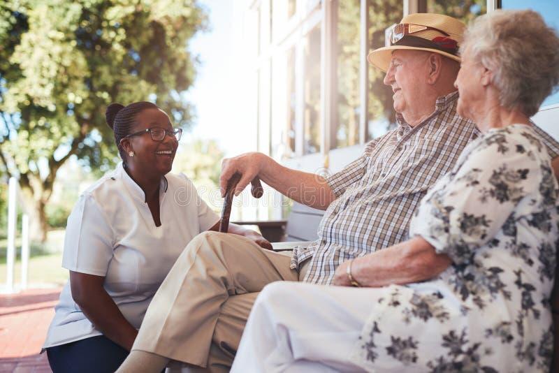Ältere Paare mit der Pflegekraft, die draußen sitzt lizenzfreies stockbild