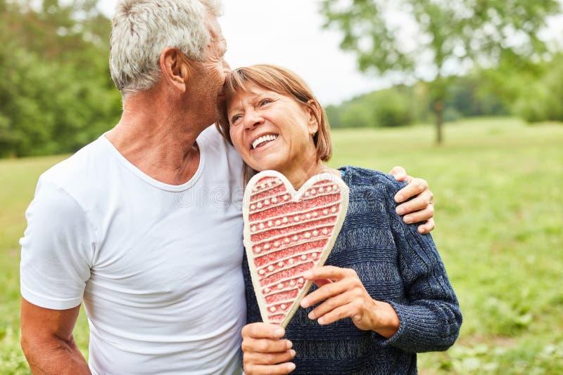 Ältere Paare mit einem Lebkuchenherzen lizenzfreie stockfotos