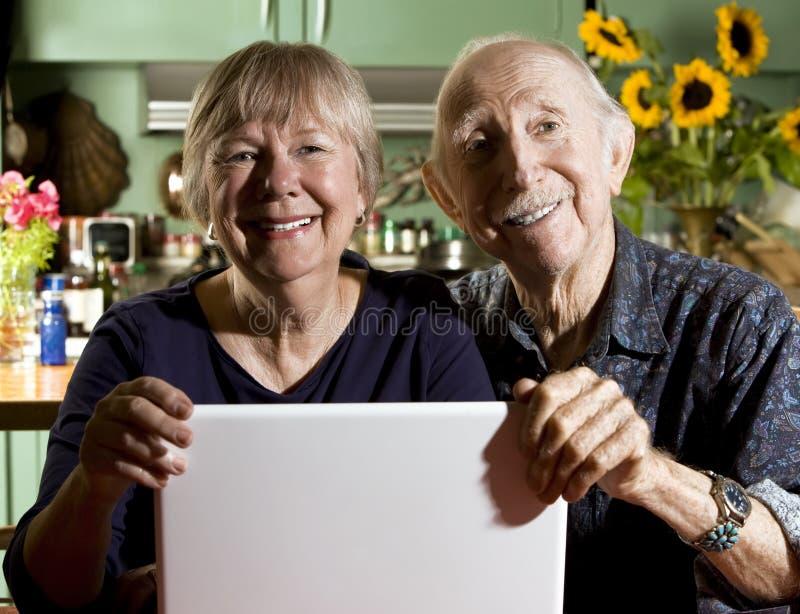 Ältere Paare mit einer Laptop-Computer lizenzfreies stockbild
