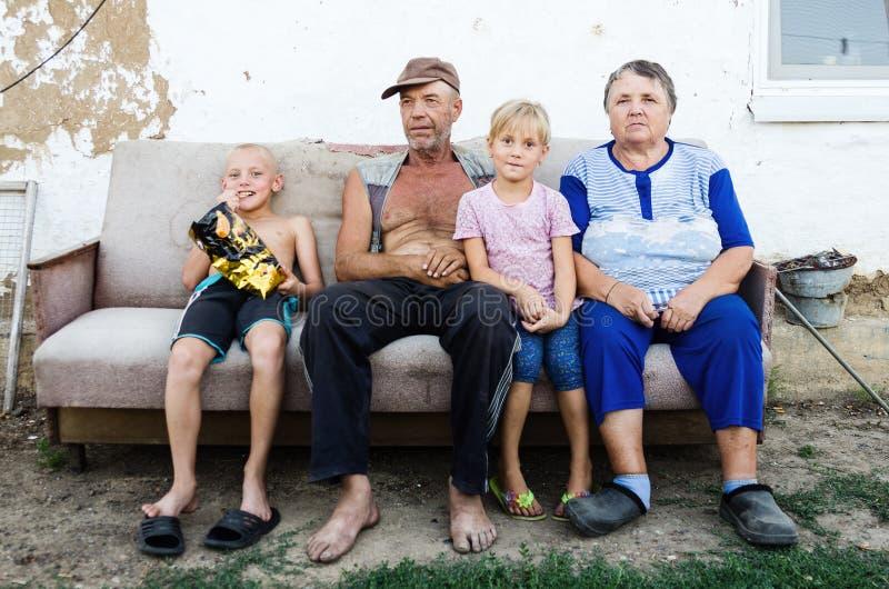 Ältere Paare mit ihren Enkelkindern im Yard eines Dorfhauses lizenzfreie stockfotografie